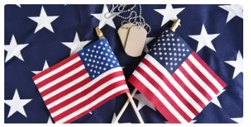 Two small flags laying on top of a larger flag showing just the white stars.