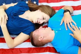A woman and a man laying on an American Flag